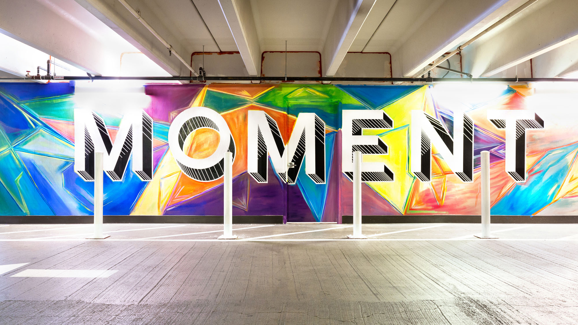 "Colorful mural that reads ""MOMENT"" on a wall in a parking garage off of San Pedro Street in San Jose"