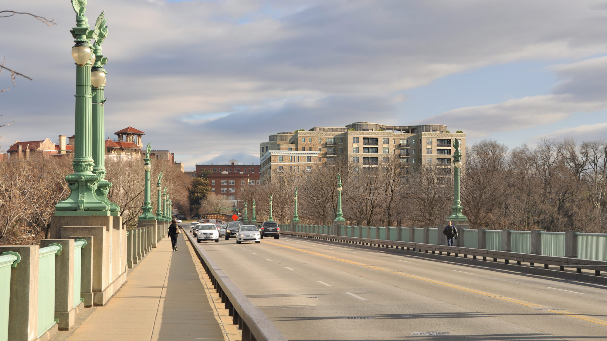 A view of a bridge with two multi-story residential buildings in the distance.