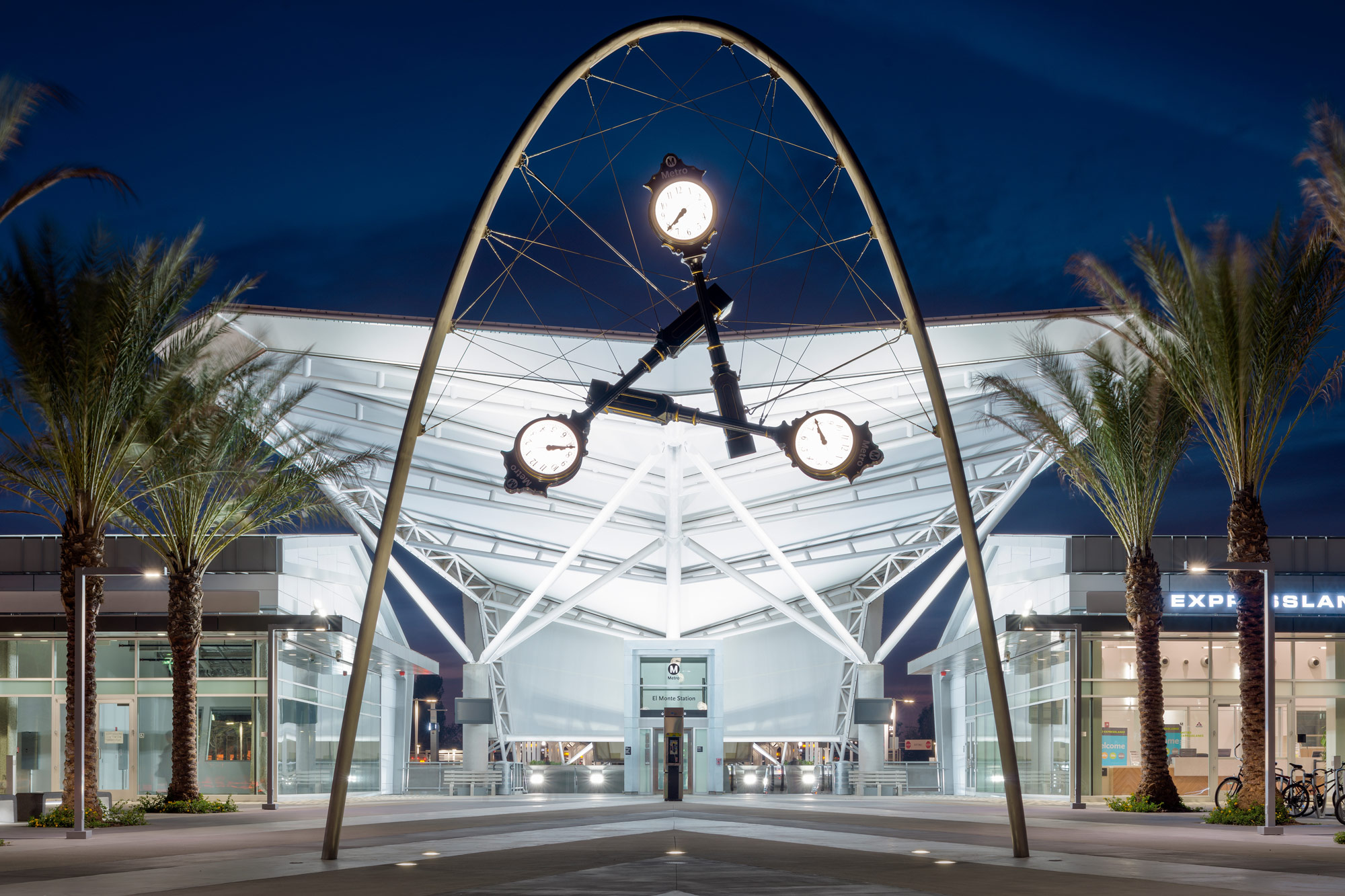 A sculpture of three suspended vintage clocks outside bus station plaza at night.