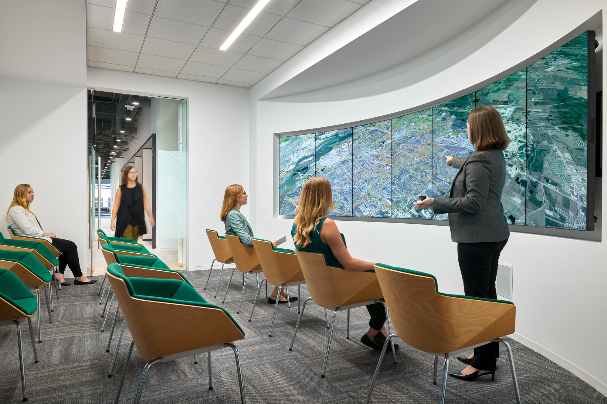 A person points to a panoramic video wall showing satellite images in front of a conference room.
