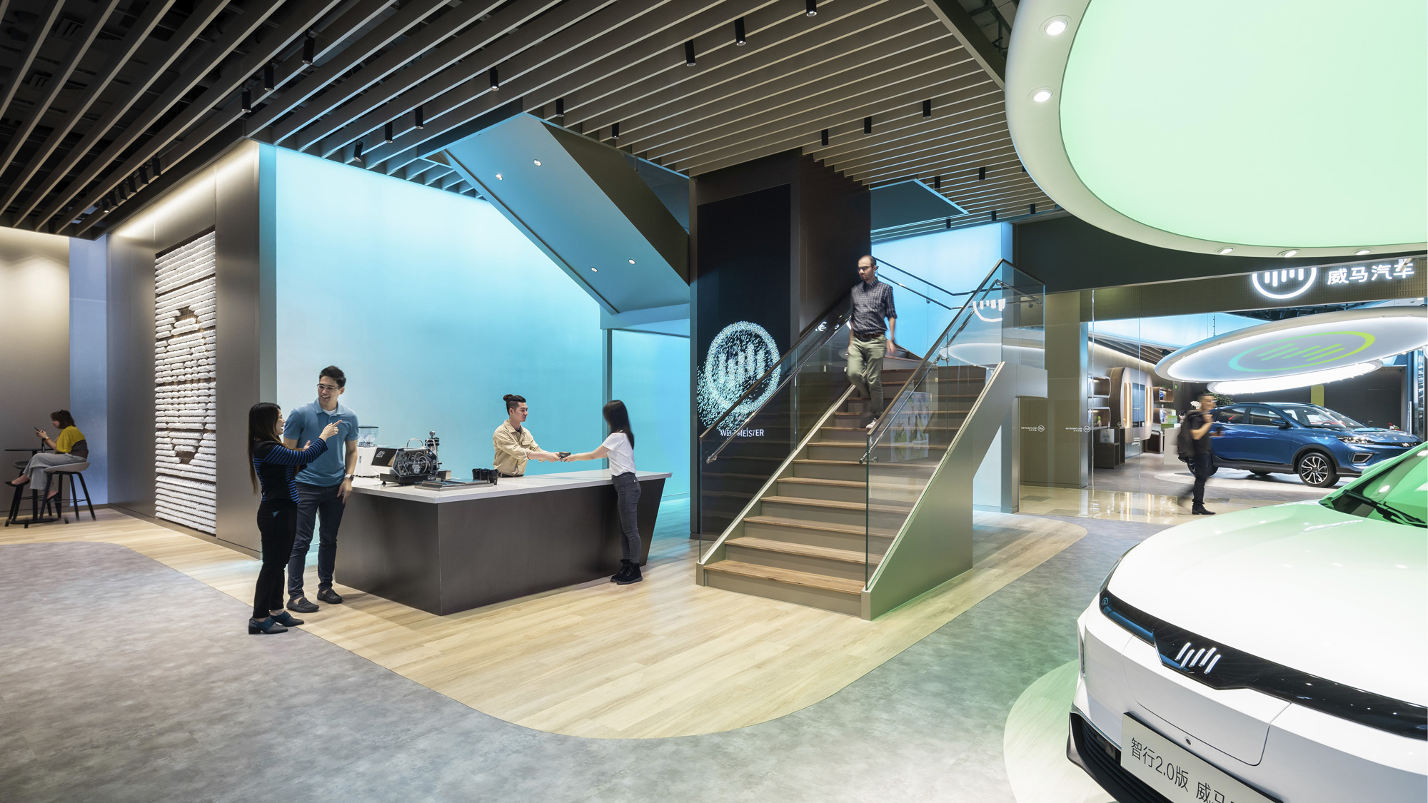 Visitors stand at a coffee bar next to a staircase and an electric vehicle showroom.